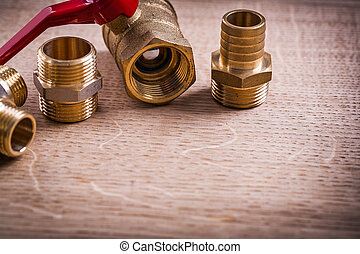 Plumbing Tools Brass Pipe Connectors On Wooden Board Close Up