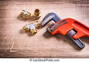 Plumbing Tools Composition Of Brass Pipe Connectors On Wooden Bo