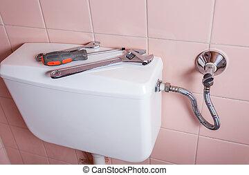 Plumbing tools lying on toilet