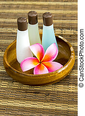 Plumeria and shampoo bottles in wooden bowl - spa concept