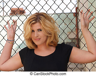 Plump blond woman against chain linked fence