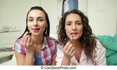 Plumping Lips - Girls putting on lip gloss on their lips and...