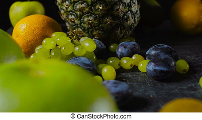 Plums and Grapes on Wooden Table with Tropical Fruits