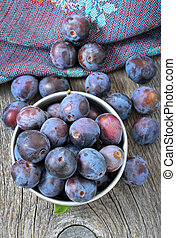 Plums in bowl on the wooden table, top view