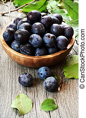 Plums in wooden bowl