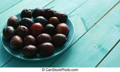 Plums on blue plate on table - Blue plate with wet ripe...