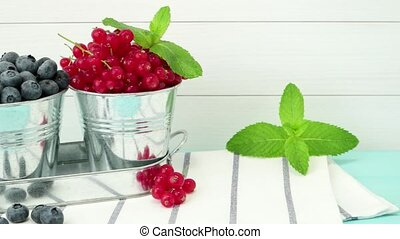 Plums, red currants and blueberries in small metal bucket on...