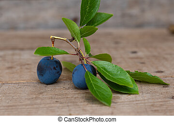Plums with leafs on wooden background