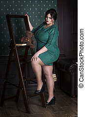 Plus size fashion model in green evening dress, fat woman on luxury interior, overweight female body