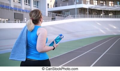 Plus size female walking along track after running -...