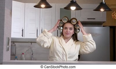 Plus size girl dressed in a bathrobe, curlers on her head, admiring herself in the mirror
