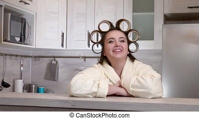 Plus-size girl dressed in a bathrobe, curlers on her head, emotionally speaks to camera