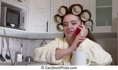 Plus-size girl, dressed in a bathrobe, curlers on her head, talking by phone sitting at kitchen