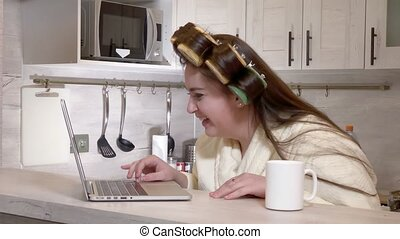 Plus-size girl, dressed in a bathrobe, curlers on her head, talking by video call