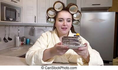 Plus-size girl, dressed in bathrobe, curlers on her head, examines a large piece of cake,