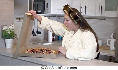 Plus-size girl, dressed in a bathrobe, curlers on her head, opening box with pizza inside in the kitchen and enjoying it