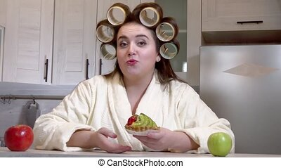 Plus-size girl with curlers on her head dressed in a bathrobe is recording a video blog