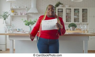 Joyful charming plus size african american female with afro braids demonstrating inspiring body positive placard, saying my body is perfect indoors, feeling beautiful, happy and confident.