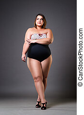 Plus size model in sexy swimsuit, fat woman on gray background, overweight female body