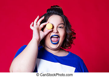 Plus size model with wide open mouth and blue lipstick posing with macaroon on red background