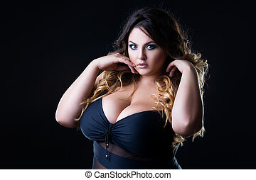 Plus size sexy fashion model in lingerie, fat woman with big natural on black studio background