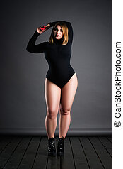 Plus size sexy model in black bodysuit, fat woman on gray studio background, overweight female body