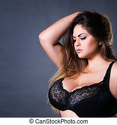 Plus size sexy model in black bra, fat woman with big natural on gray studio background, overweight female body