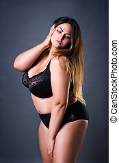 Plus size sexy model in black lingerie, fat woman on gray studio background, overweight female body