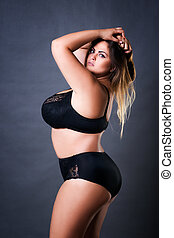 Plus size sexy model in black underwear, fat woman on gray studio background, overweight female body