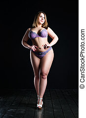 Plus size sexy model in lingerie, fat woman on black studio background, overweight female body