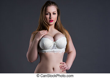 Plus size sexy model in white bra, fat woman with big natural breast on gray studio background, overweight female body
