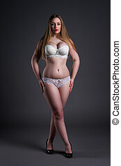 Plus size sexy model in white underwear, fat woman on gray studio background, overweight female body