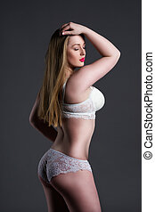 Plus size sexy model in white underwear, fat woman with big natural breast on gray studio background, overweight female body