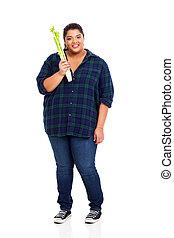 plus size teenager holding celery