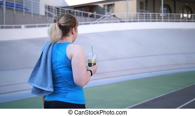 Plus size woman jogger walking with smoothie drink - Rear...