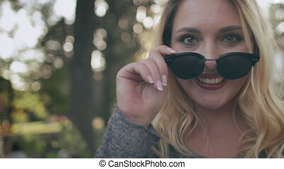 Plus size woman smiling in sunglasses. Closeup bokeh portrait. Nature landscape at summer sunny day. Surprising and flirt at park. Body positive girl. Blond model rest at green trees. Sun holiday walk