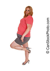 Plus size woman standing in shorts and heels.