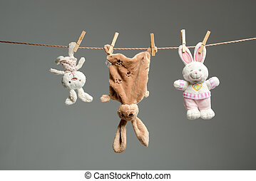 Plush bunnies on the clothesline, on gray background