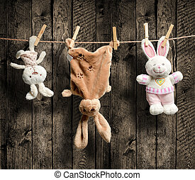 Plush bunnies on the clothesline, wooden background