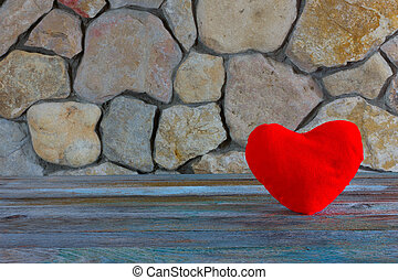 plush red heart on the background of a stone wall,