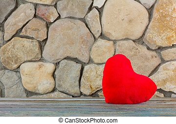plush red heart on the background of a stone wall