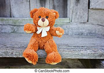 Plush Teddy Bear toy sitting on a wood