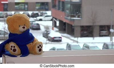 Plush teddy bear with blue scarf sitting on radiator near window. Snow falling