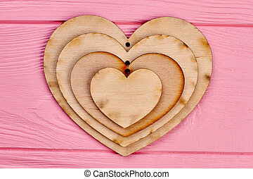 Plywood hearts collection on pink wood.