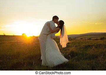 poślubna para, na, zachód słońca