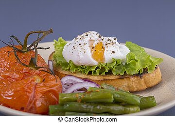 Poached egg on a piece of bread with fried green beans, tomato and arugula on a plate