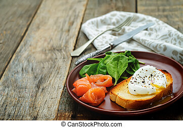 poached egg with salmon and spinach on a dark wood...