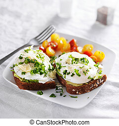 poached eggs and avocado on toast with tomatoes