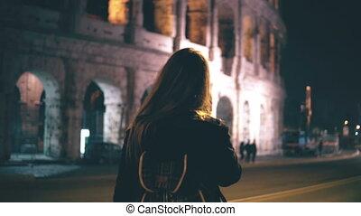 pociągający, kobieta stanie, blisko, colosseum, w, rzym, włochy, i, używając, smartphone., dziewczyna, pieszy i mówiący, na, przedimek określony przed rzeczownikami, głoska.