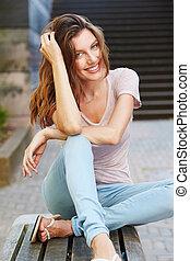 pociągający, młoda kobieta, posiedzenie na ławie, outdoors